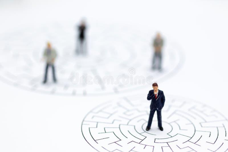 Gente miniatura: Hombres de negocios en el laberinto Uso de la imagen para al solenoide imagen de archivo libre de regalías