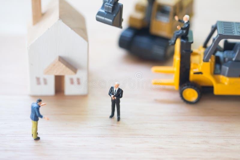 Gente miniatura: Il banchiere afferra il bene Sfratto e confisca forzati fotografie stock