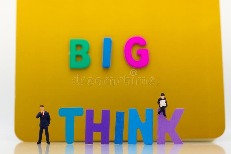 Gente miniatura: L'uomo d'affari con testo PENSA GRANDE Uso di immagine per l'idea, concetto di affari fotografia stock libera da diritti
