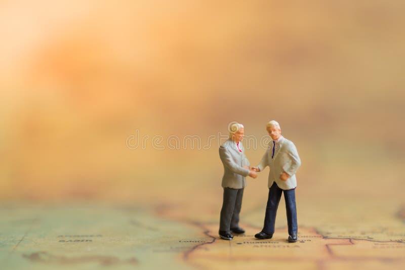 Gente miniatura: L'uomo di affari fa un affare, concetto di riunione del socio commerciale immagini stock libere da diritti