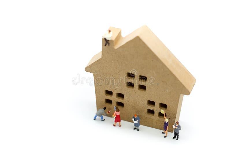 Gente miniatura: la gente che legge un libro con il giocattolo di legno della casa, immagini stock libere da diritti