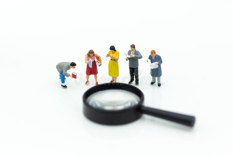 Gente miniatura: Los estudiantes leyeron los libros con la lupa Uso de la imagen para el concepto de la educación imagen de archivo libre de regalías