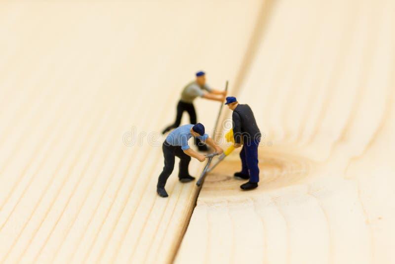 Gente miniatura: Los trabajadores están utilizando el equipo de perforación de madera Uso de la imagen para la construcción, conc imagen de archivo