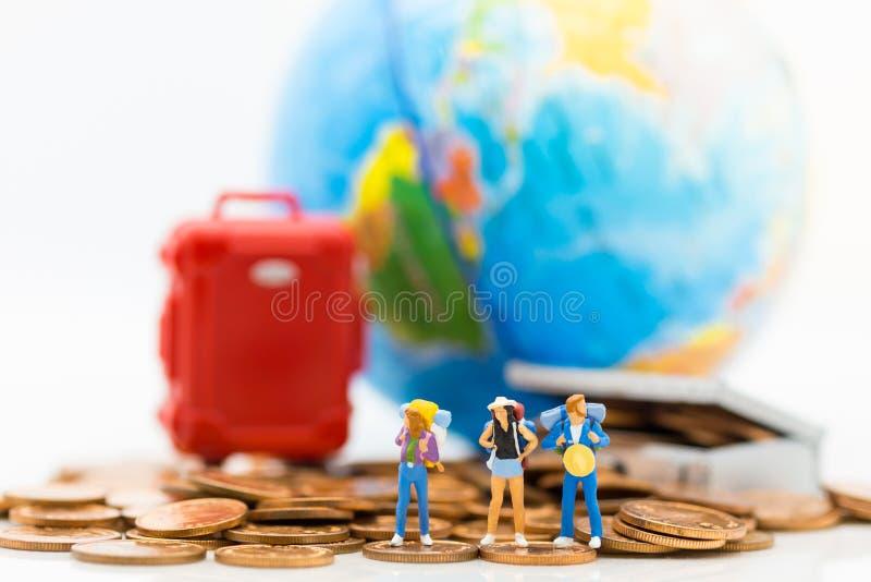 Gente miniatura: Los viajeros se colocan en una pila de monedas y tienen una maleta roja, mapa del mundo para el fondo Uso de la  fotografía de archivo
