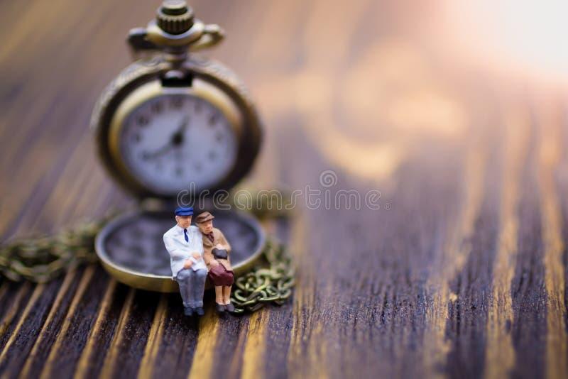 Gente miniatura: Los viejos pares se están sentando en el reloj Uso de la imagen para pasar minutos preciosos cada minuto juntos fotografía de archivo