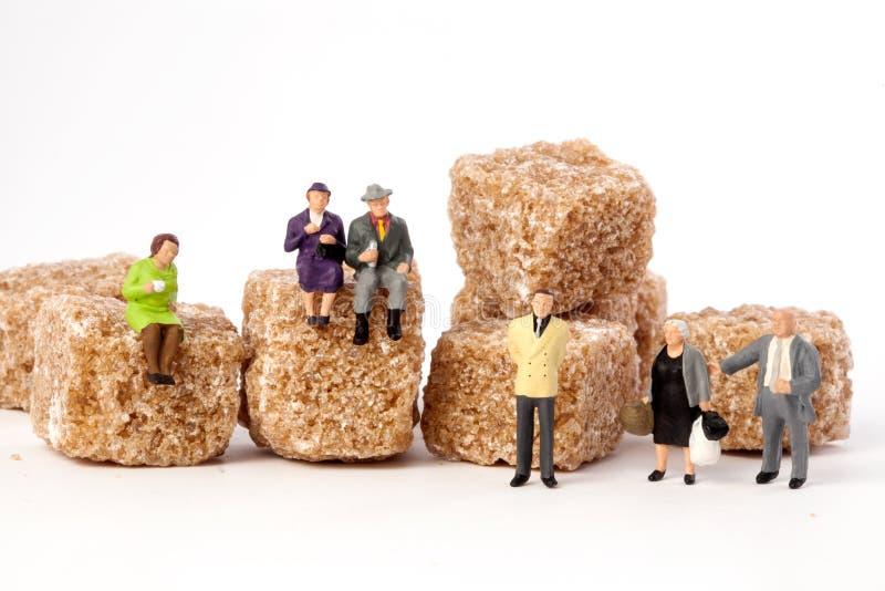 Gente miniatura: mayores, en frente, cubos del azúcar marrón imagen de archivo