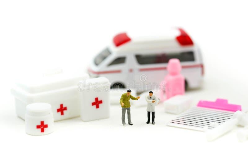 Gente miniatura: Medico e paramedico che presente al paziente in ambulanza, concetto dell'ambulanza della medicina fotografie stock libere da diritti