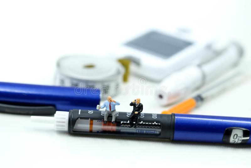 Gente miniatura: Medico e paziente con la penna dell'insulina, diabete fotografia stock