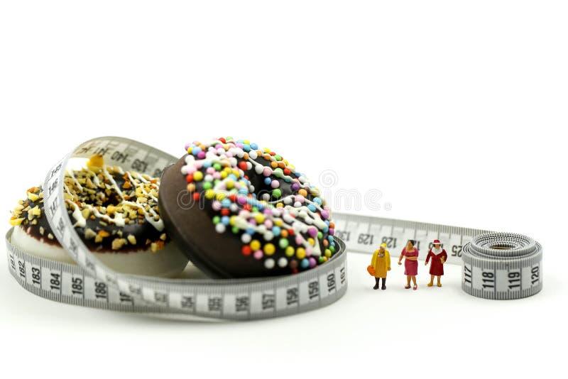 Gente miniatura: Mujer y amigo gordos con el buñuelo que ata por la cinta métrica, dietética para el concepto delgado de la forma imagen de archivo