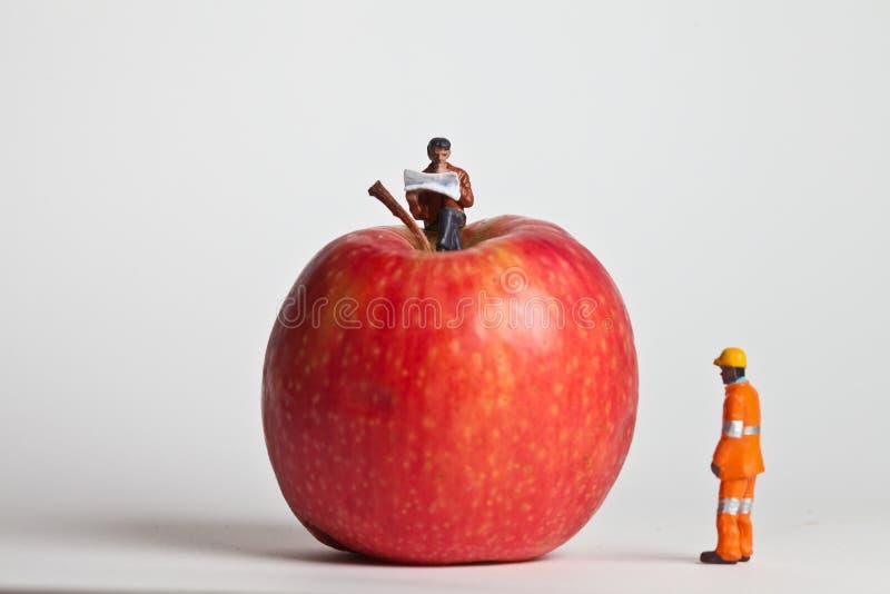 Gente miniatura nell'azione che si siede su una mela fotografia stock libera da diritti