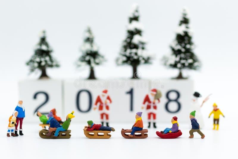 Gente miniatura: Niños que juegan en la nieve divertida junto Uso de la imagen para el festival de la Navidad imagen de archivo libre de regalías