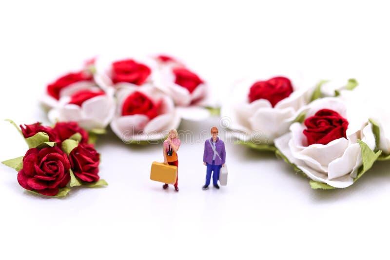 Gente miniatura: Pares del amor con las rosas rojas y las rosas blancas fotografía de archivo libre de regalías