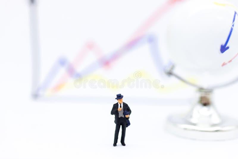 Gente miniatura: Parte anteriore del supporto dell'uomo d'affari del cruscotto, grafici dell'esposizione, margini di guadagno di  immagine stock libera da diritti