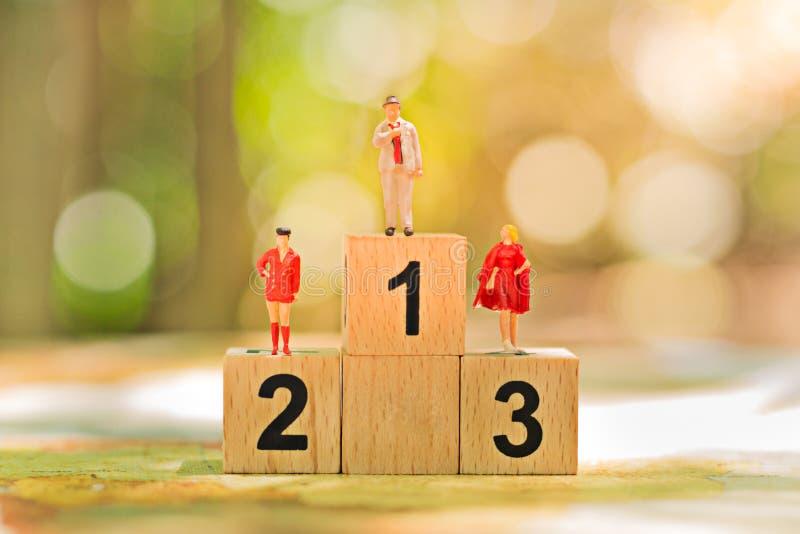 Gente miniatura: Piccole figure del lavoratore con la condizione di legno del podio Concetto della concorrenza del gruppo di affa immagine stock libera da diritti