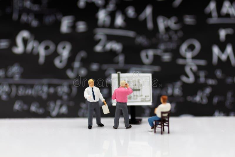 Gente miniatura: Processo del lavoro di pianificazione dell'uomo d'affari L'uso di immagine per l'individuazione della soluzione/ immagini stock
