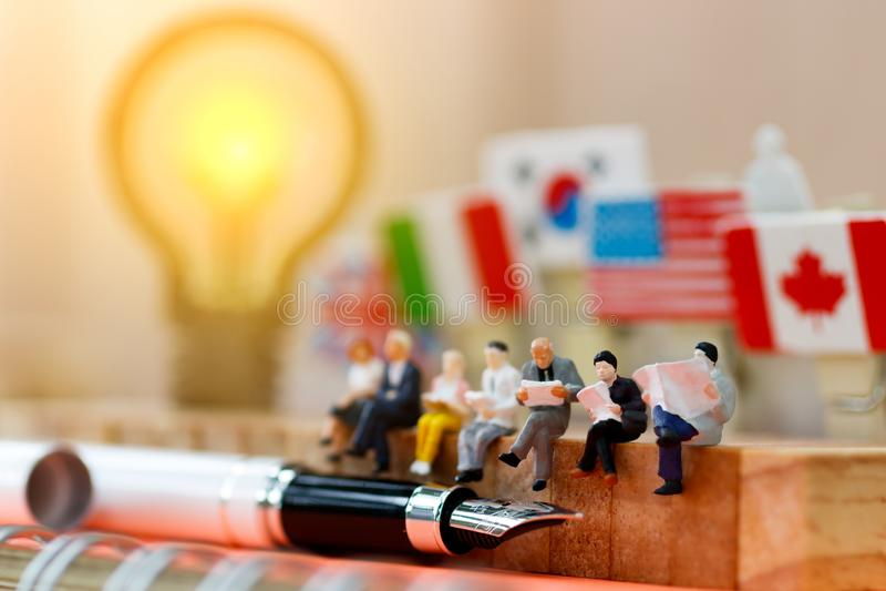 Gente miniatura que lee y que se sienta en la madera con idea de la lámpara usando como fondo, la educación o el concepto del neg imágenes de archivo libres de regalías