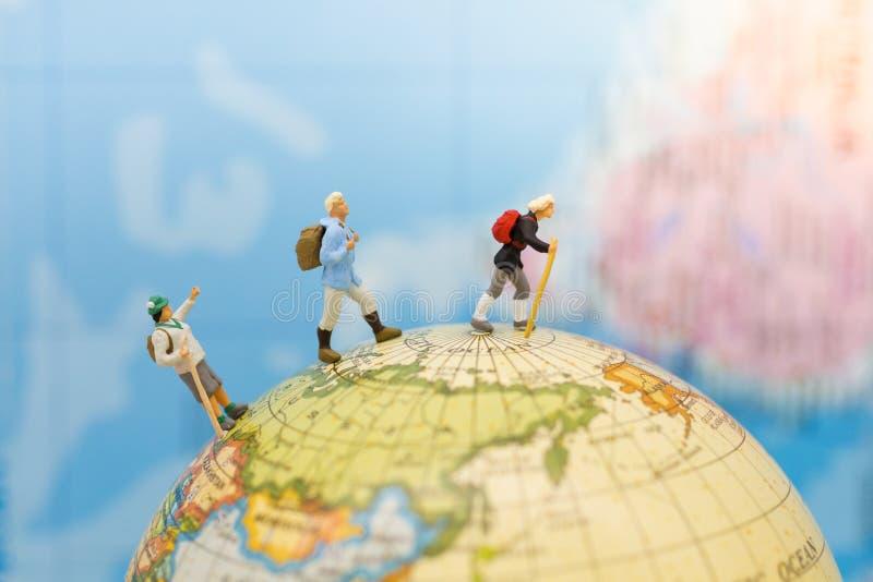 Gente miniatura: Soporte de la mochila del viajero del grupo y el caminar en mapa del mundo Uso de la imagen para el concepto del imágenes de archivo libres de regalías