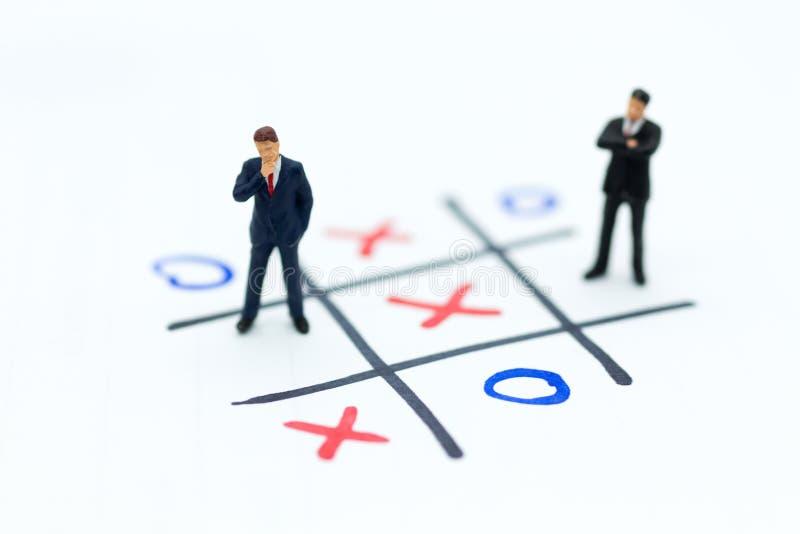 Gente miniatura: Soporte de los hombres de negocios en tablero del juego de XO Uso de la imagen para el concepto de la competenci fotos de archivo