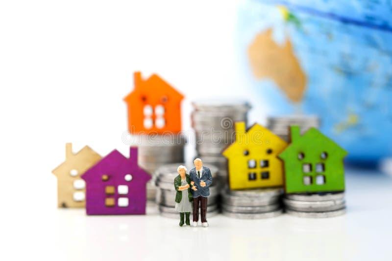 Gente miniatura: stando sulla pila delle monete con la casa, savi dei soldi immagini stock libere da diritti