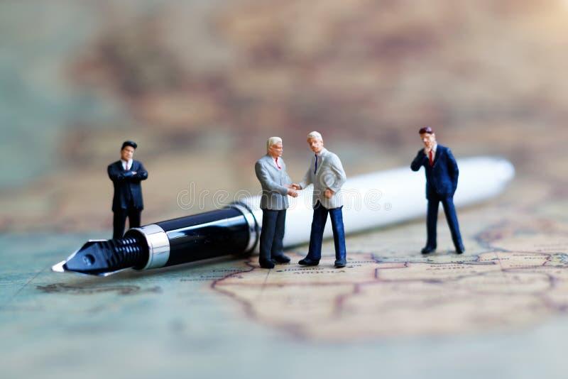 Gente miniatura: Stretta di mano dell'uomo d'affari sulla mappa di mondo fotografie stock libere da diritti