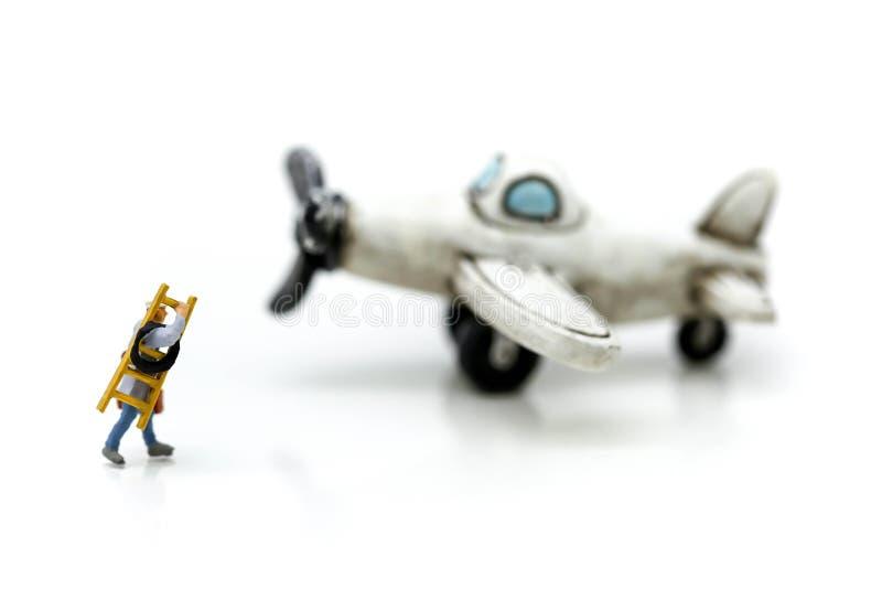 Gente miniatura: tecnico, meccanico con l'aeroplano usando per fotografie stock