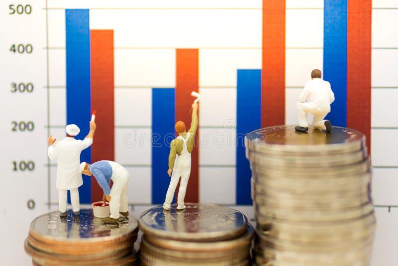 Gente miniatura: Trabajador que se coloca en la pila de monedas y de gráfico de barra de pintura fotos de archivo libres de regalías