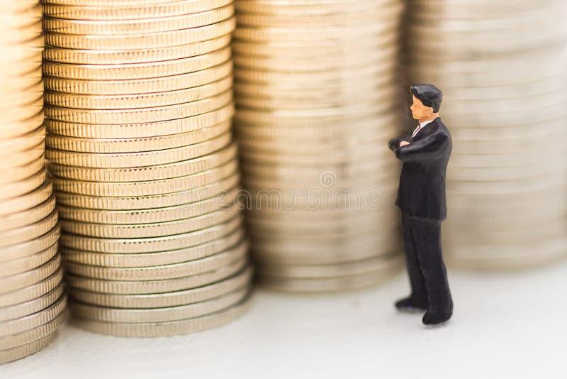 Gente miniatura, uomo d'affari che cerca pila di monete facendo uso come di crescita di soldi del fondo su, risparmiare, finanzia immagine stock libera da diritti