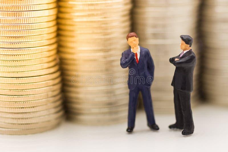 Gente miniatura, uomo d'affari che cerca pila di monete facendo uso come di crescita di soldi del fondo su, risparmiare, finanzia immagini stock