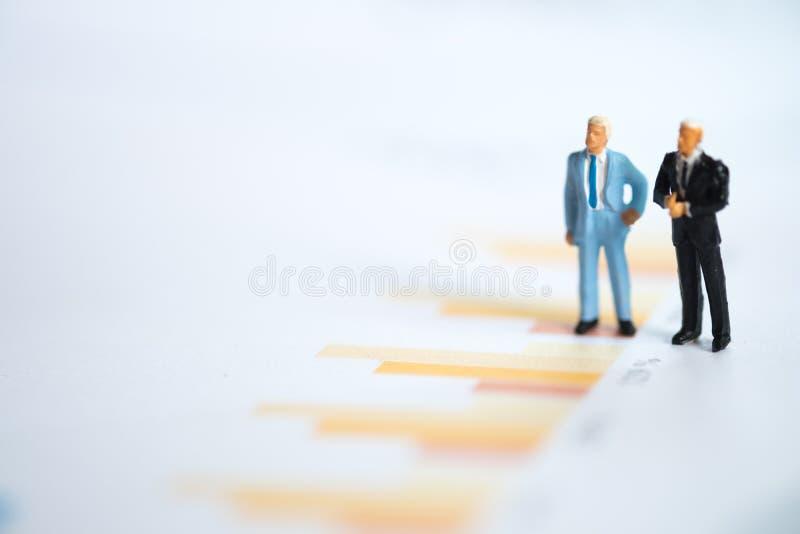 Gente miniatura: Uomo d'affari che pensa con il progetto per l'investimento fotografia stock libera da diritti