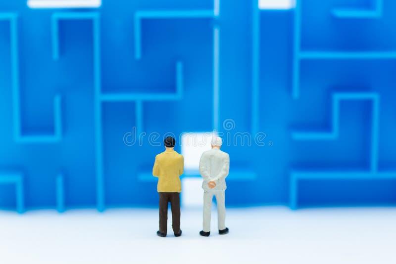 Gente miniatura: Uomo d'affari che sta con il labirinto L'uso di immagine per l'individuazione della soluzione per risolve il pro immagine stock