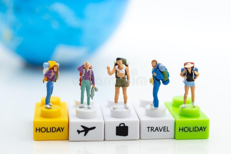 Gente miniatura: Viaje del grupo del Backpacker encendido en todo el mundo Uso de la imagen para el viaje, concepto del negocio imagenes de archivo