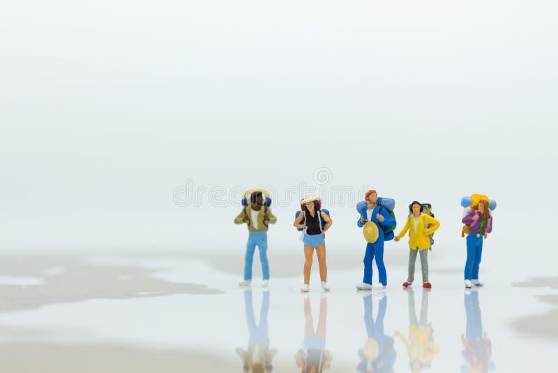 Gente miniatura: Viajeros que se colocan en un mapa del mundo Uso de la imagen para el viaje, concepto del negocio fotografía de archivo libre de regalías