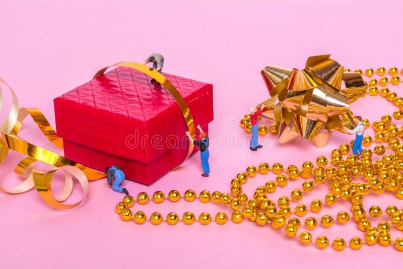Gente miniatura y una caja de regalo en un fondo rosado Proceso de los regalos del embalaje fotos de archivo libres de regalías