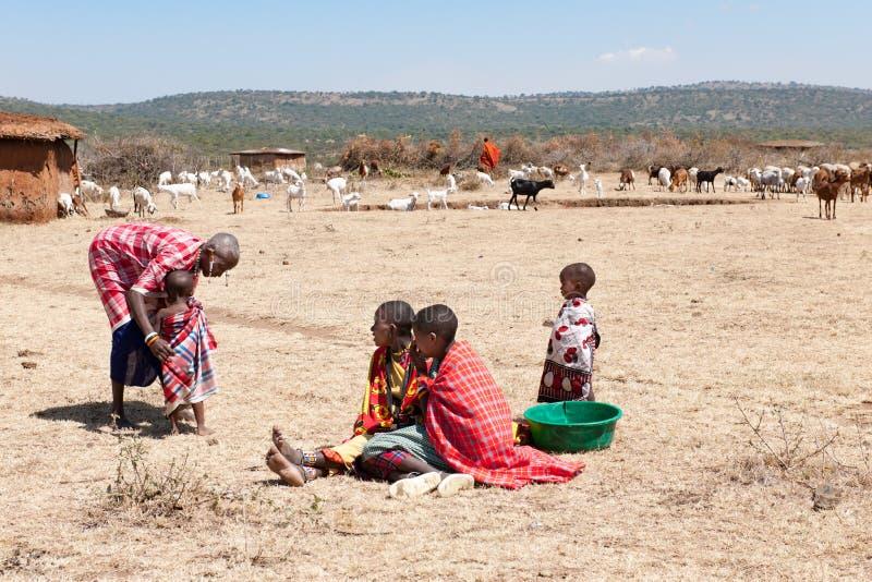 Gente, mujeres y niños del Masai de la tribu de Maasai sentándose en la tierra, Tanzania, África imágenes de archivo libres de regalías