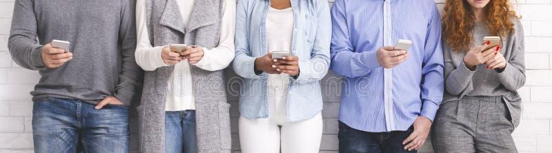 Gente multietnica che giudica i telefoni e lettura rapida, stanti nella fila fotografia stock