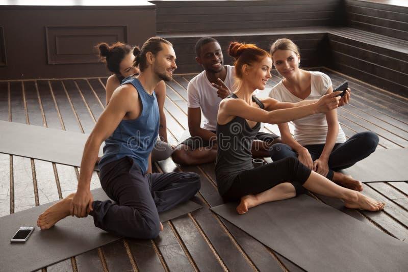Gente multirazziale sorridente che fa selfie sullo smartphone all'yoga t fotografie stock libere da diritti