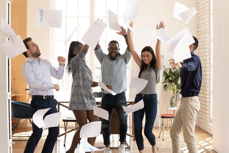Gente multirracial extática del equipo del negocio que lanza los papeles que bailan en oficina imagen de archivo