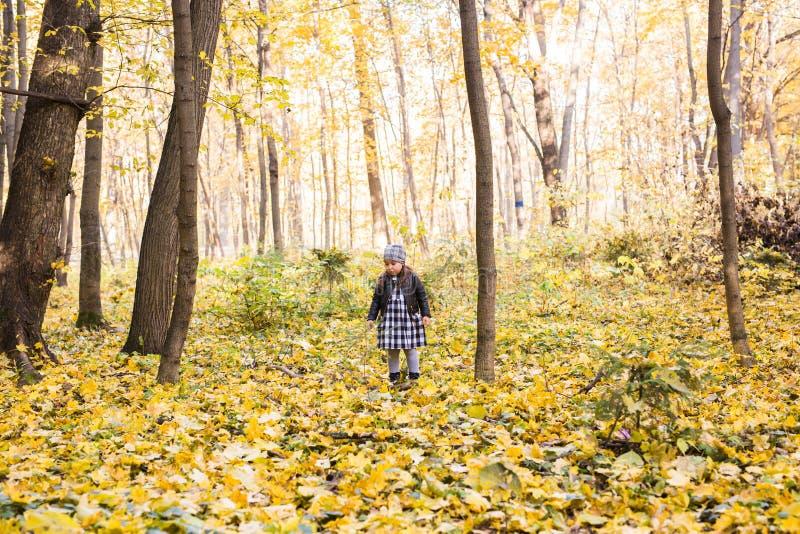 Gente, niños y concepto de la naturaleza - la niña sonriente en otoño parquea foto de archivo