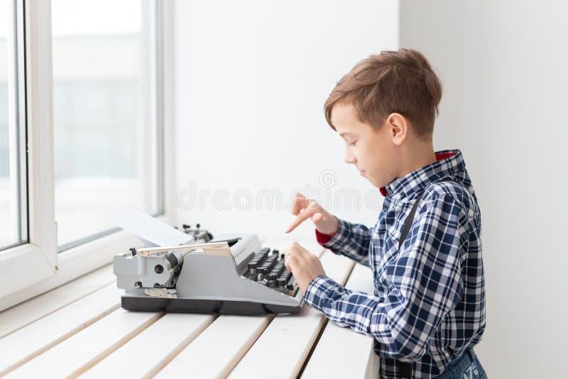Gente, niños y concepto del estilo - muchacho joven con la máquina de escribir negra vieja en el fondo blanco imagenes de archivo