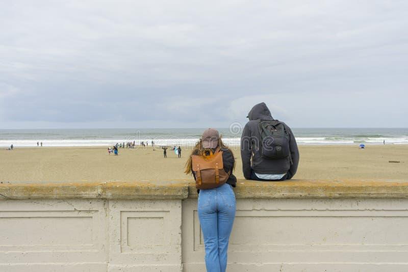 Gente no identificada que camina en los hoyos del fuego de la playa del océano en San Francisco, CA imagen de archivo