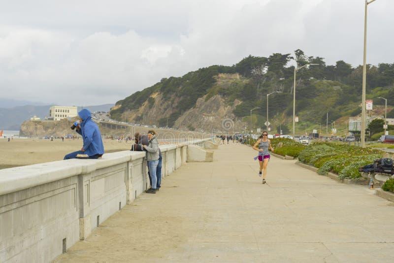 Gente no identificada que camina en los hoyos del fuego de la playa del océano en San Francisco, CA fotos de archivo