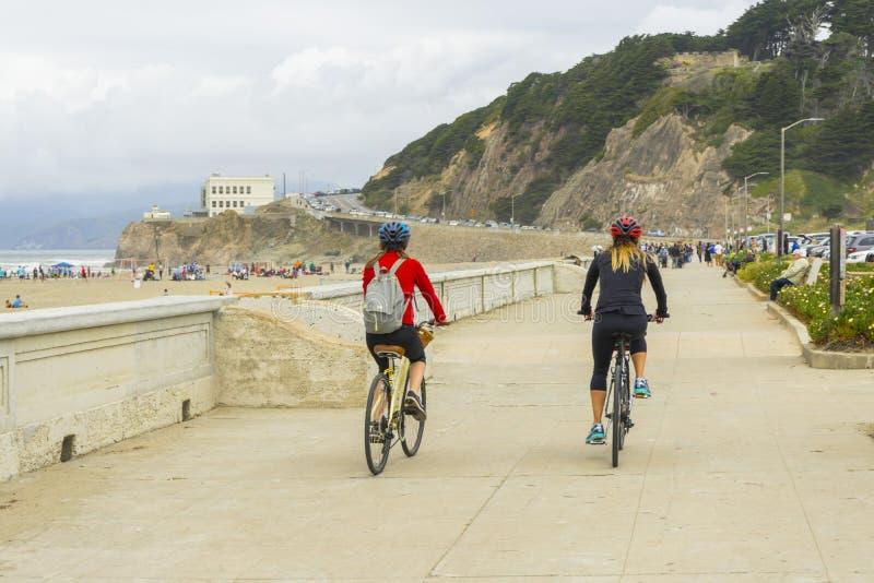 Gente no identificada que camina en los hoyos del fuego de la playa del océano en San Francisco, CA foto de archivo libre de regalías