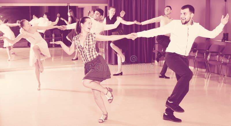 Gente ordinaria del grupo que baila el salto lindy en pares fotografía de archivo