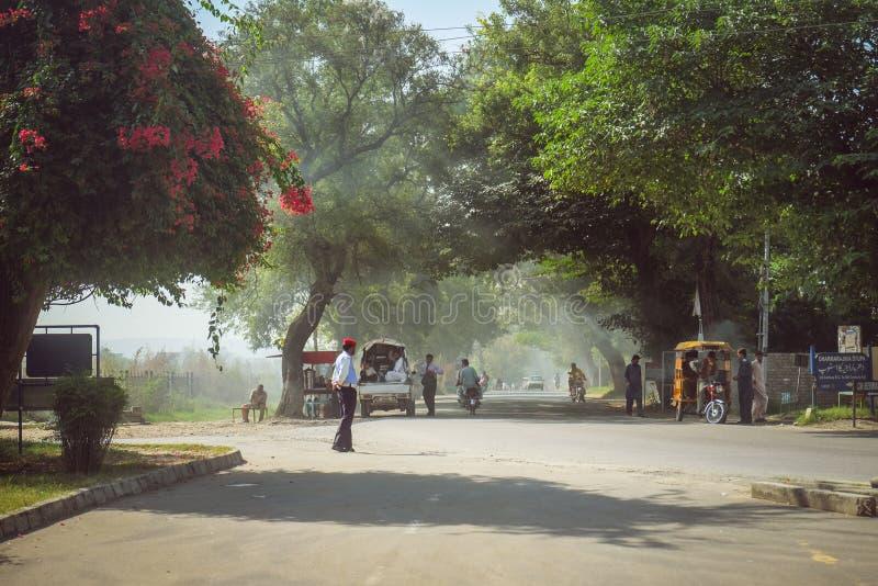 Gente paquistaní en la calle sombría delante del museo de Taxila, Punjab fotos de archivo