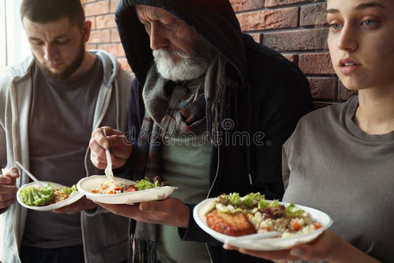 Gente pobre con las placas de la comida en la pared fotos de archivo