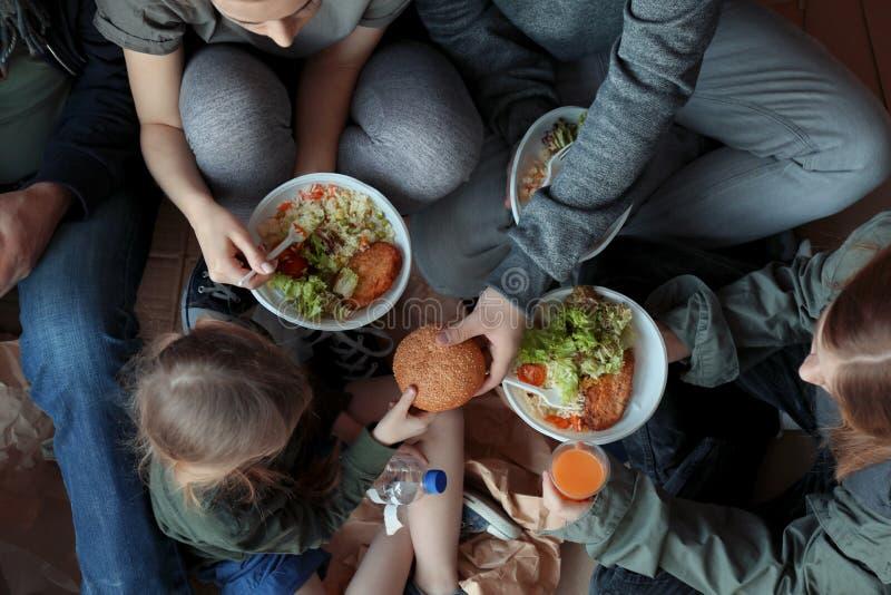 Gente pobre con las placas de la comida que se sientan en piso fotografía de archivo