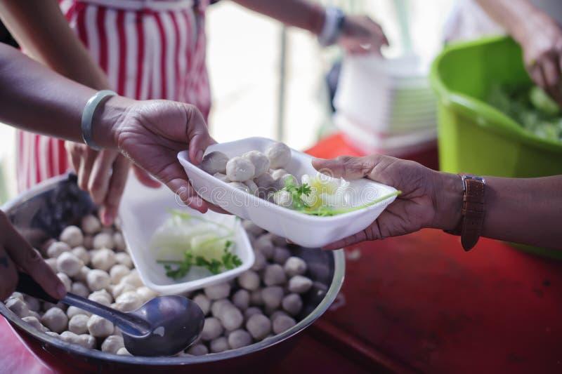 Gente pobre que recibe la comida de donaciones: Ayudan al vagabundo con el alivio de comida, alivio del hambre: voluntarios que d imágenes de archivo libres de regalías