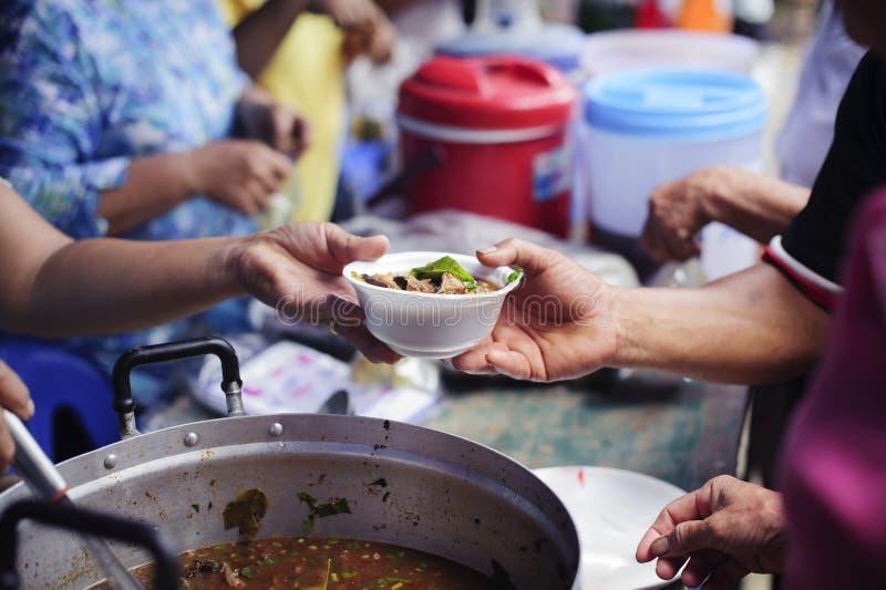 Gente pobre que recibe la comida de donaciones: Ayudan al vagabundo con el alivio de comida, alivio del hambre: voluntarios que d foto de archivo libre de regalías