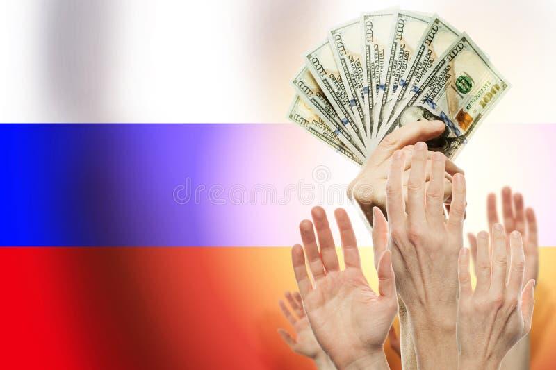 Gente que aumenta las manos con los d?lares y la bandera Rusia en fondo Concepto del dinero fotografía de archivo