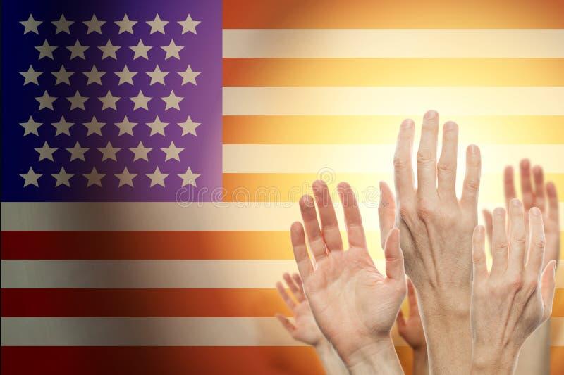 Gente que aumenta las manos y la bandera americana en fondo Concepto patri?tico imagen de archivo libre de regalías